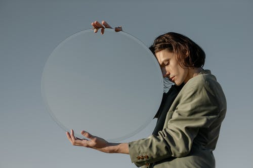 Girl in Green Jacket Holding Clear Glass Ball