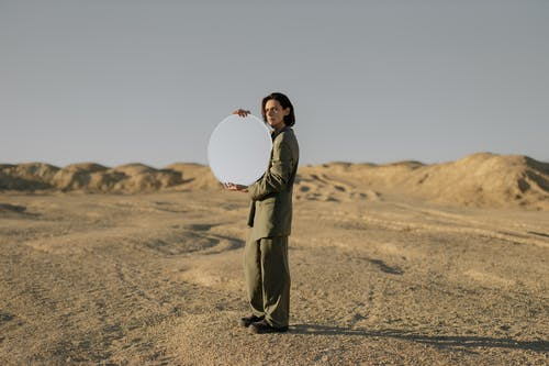 Man in Brown Coat Holding White Round Paper