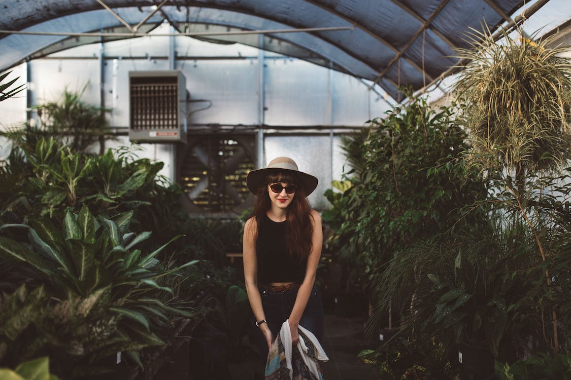 Woman Wearing Black Tank Dress and Hat in Greenhouse