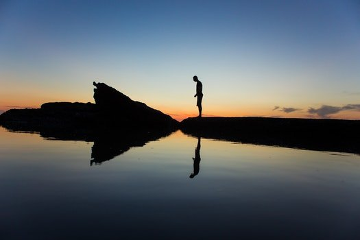 Silhouette of Man Standing Near Body of Water during Yellow Sunset