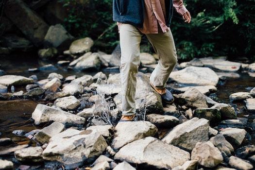 Man Trekking Rocky Stream during Daytime