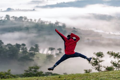 Full body of faceless male in outerwear jumping on high hill slope against foggy highlands with trees at daylight