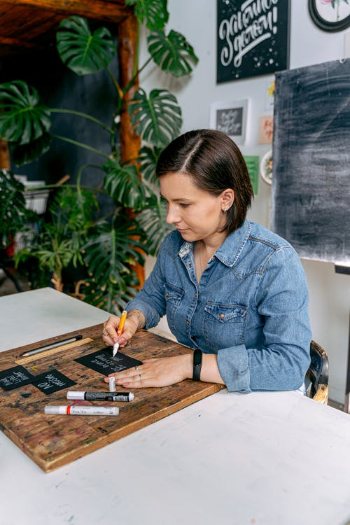 Woman in Blue Denim Jacket Writing on White Paper