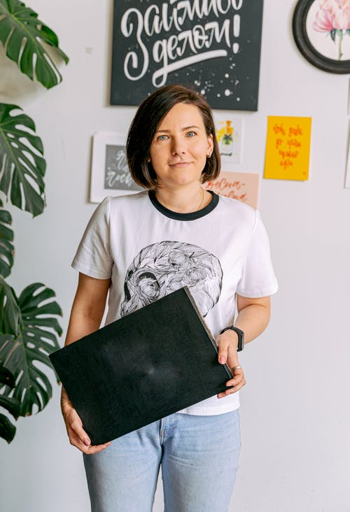 Woman in White Crew Neck T-shirt Holding Black Leather Book
