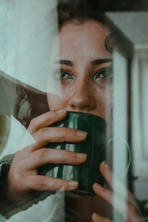 Through glass view of young thoughtful female sipping from green mug looking dreamily away