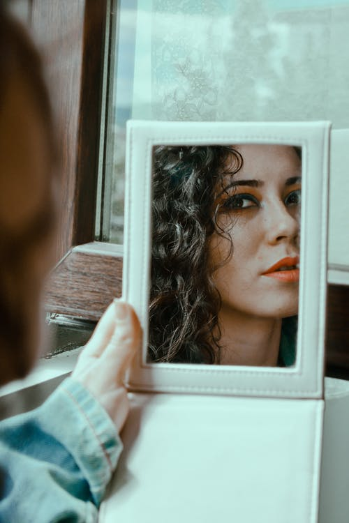 Woman looking at mirror in daylight