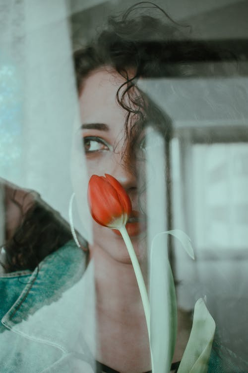 Mysterious woman with bright red tulip