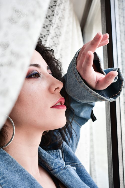 Stylish woman with bright makeup looking in window