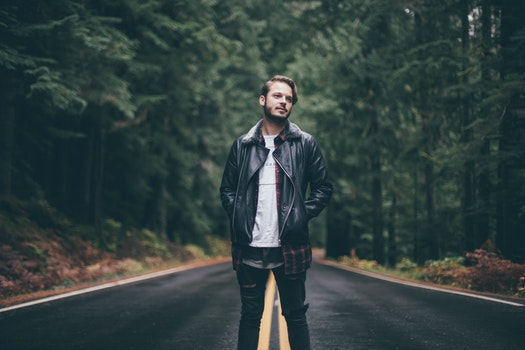 Man Wearing Black Leather Jacket Standing on Highway in the Middle of Green Trees