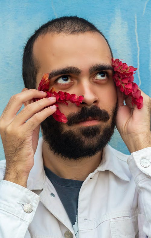 Man in White Dress Shirt With Red Flower on His Ear