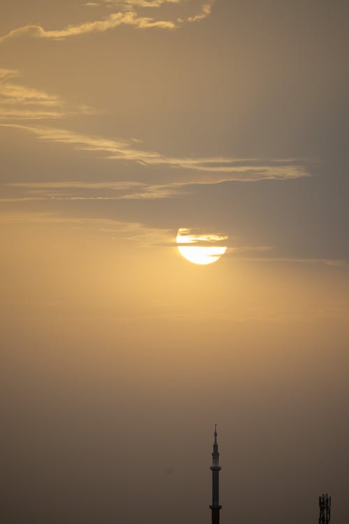 Picturesque view of bright yellow sun behind clouds in evening above tower of oriental building
