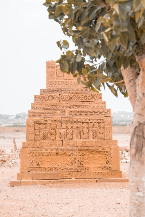 Historic tomb with carved patterns placed behind tree