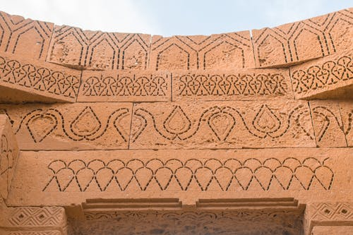 Ancient sandstone facade with carved symmetrical ornament on cloudy day