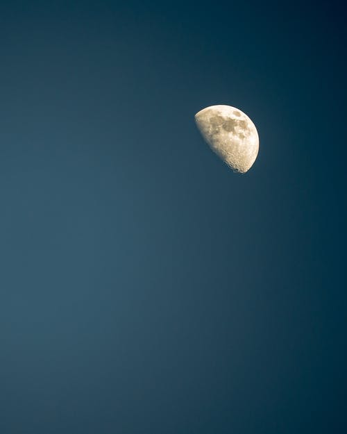 Half moon against dark blue sky at night