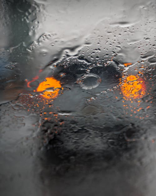 Wet glass with rain drops and spots located in front of blurred modern car with glowing orange headlights