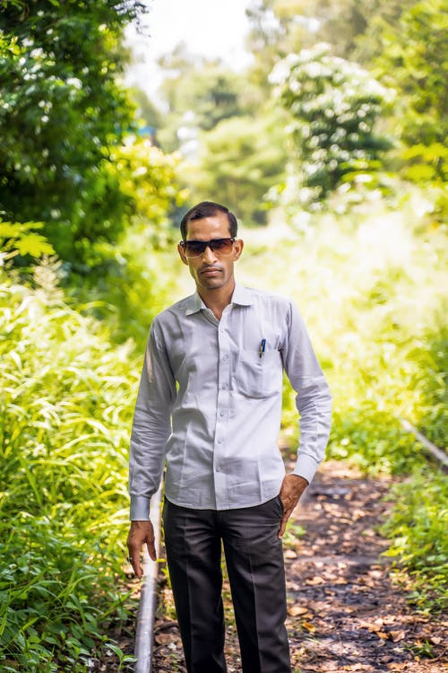 Man in White Dress Shirt and Black Pants Wearing Black Sunglasses Standing on Forest