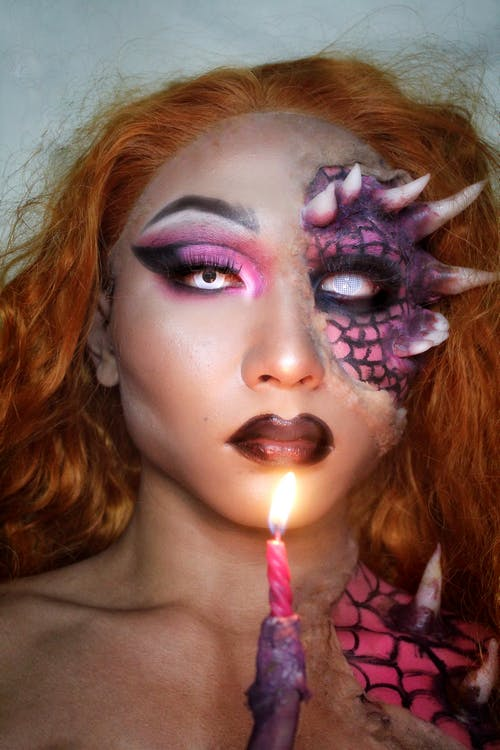 Person with unusual cool Halloween makeup holding glowing candle and looking at camera