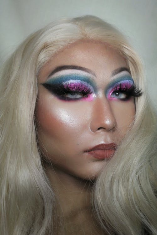 Person with bright shimmering makeup and dyed hair
