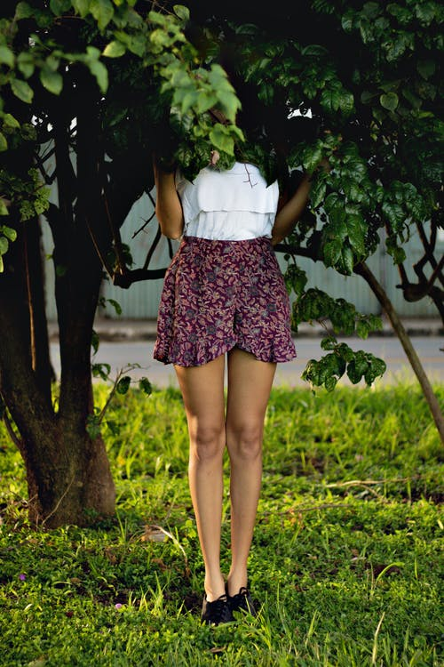 Young woman hiding in green foliage