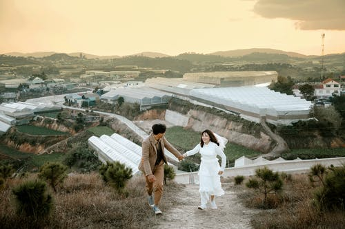 Full body of young Asian newlyweds in wedding outfits walking together on grassy hill slope and holding hands
