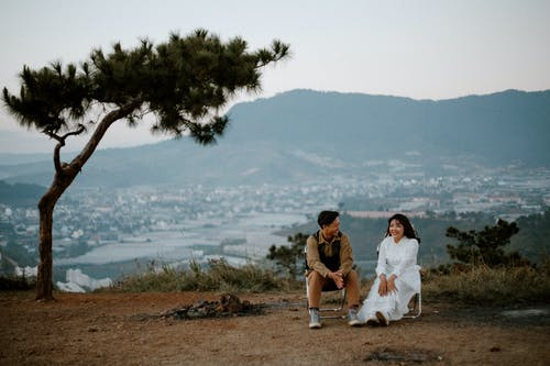 Loving couple sitting on hill above city