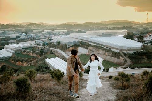 Základová fotografie zdarma na téma asijský pár, chůze, držení za ruce, dvojice
