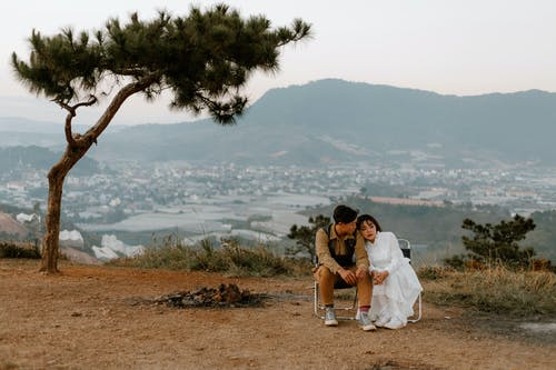 Full body of Asian couple sitting close to each other and enjoying romantic moment together