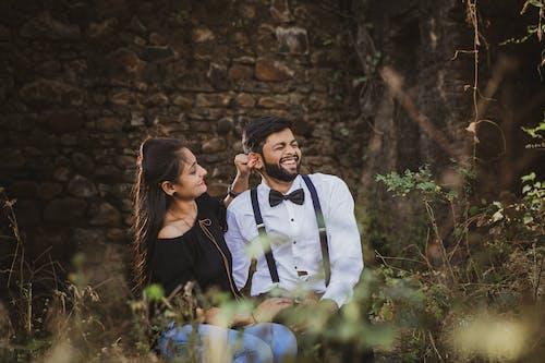 Positive ethnic couple enjoying date near brick wall