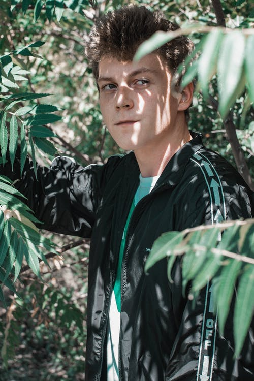Man in Black and Green Jacket Standing Near Green Leaves
