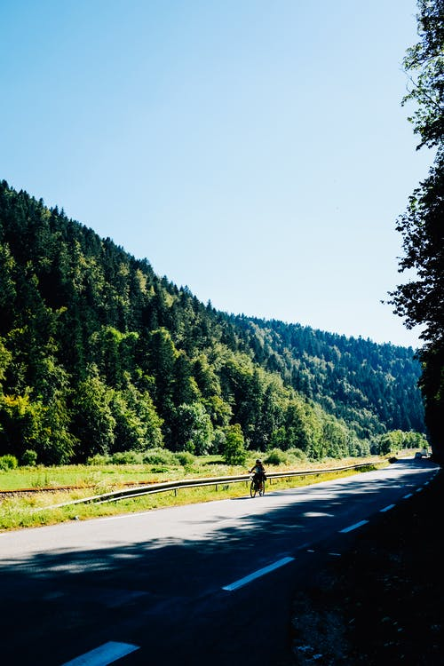Full body of anonymous person on bicycle riding on asphalt road near grassy field and hill with green forest under blue cloudless sky in countryside in sunny summer day
