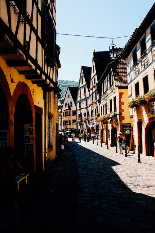 Narrow cobblestone street running between typical timbered residential houses on sunny day in German town