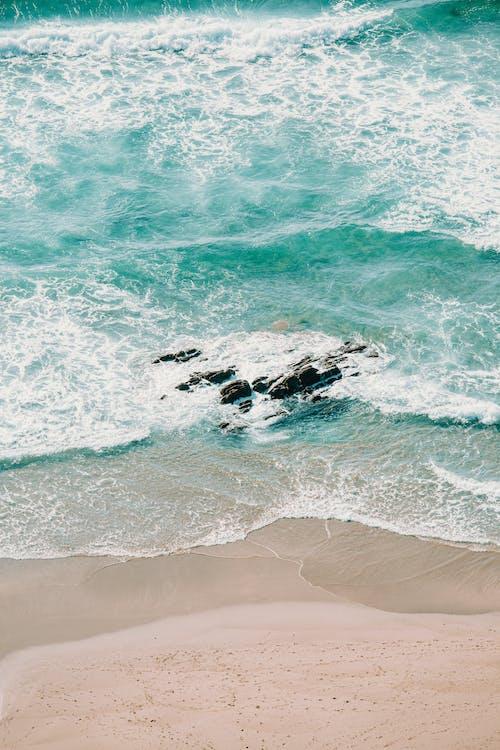 Sea waving near sandy shore