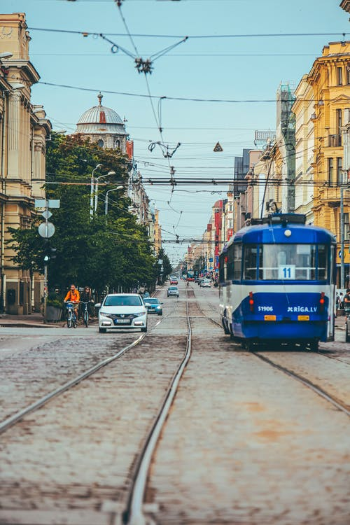 Modern tramway riding along paved city street near cars cyclists and old buildings in town
