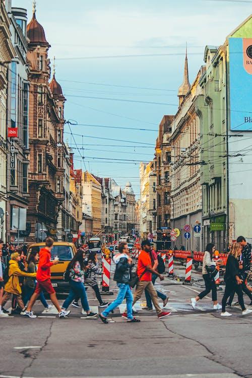 Crowd crossing road on pedestrian crossing in aged city