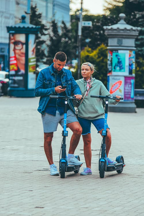 Couple with electric scooters in city park