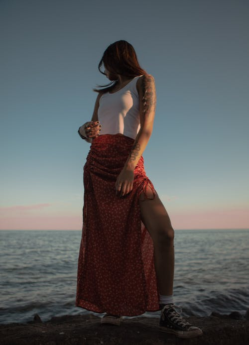 From below full body of anonymous female in long skirt and top admiring rippling sea under bright sundown sky