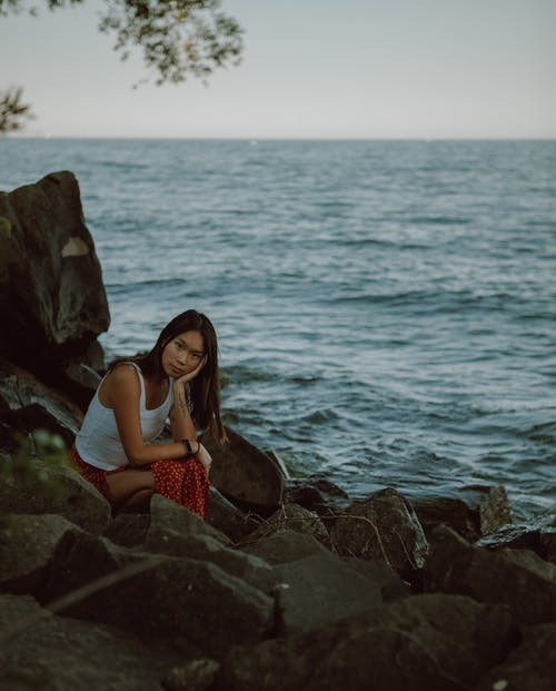 Pensive young Asian female leaning on hand while sitting on stone near rippling sea and looking at camera