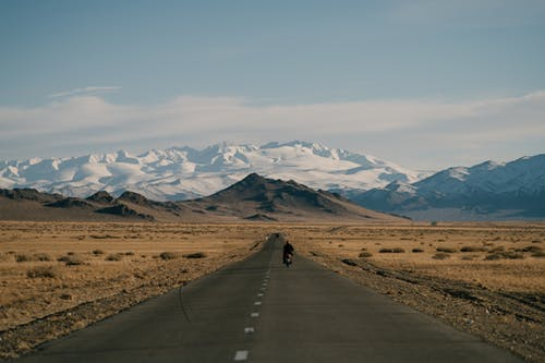 Snowy mountains behind asphalt road and hills