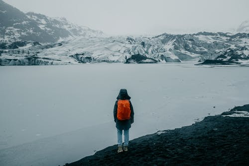 Back View of a Person in Orange Jacket Standing near the Snow Covered Ground