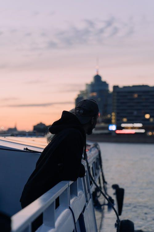 Homem De Capuz Preto E Boné Preto Sentado No Barco