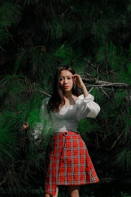 Woman in White Long Sleeve Shirt and Red and Black Plaid Skirt Standing Beside Green Plants