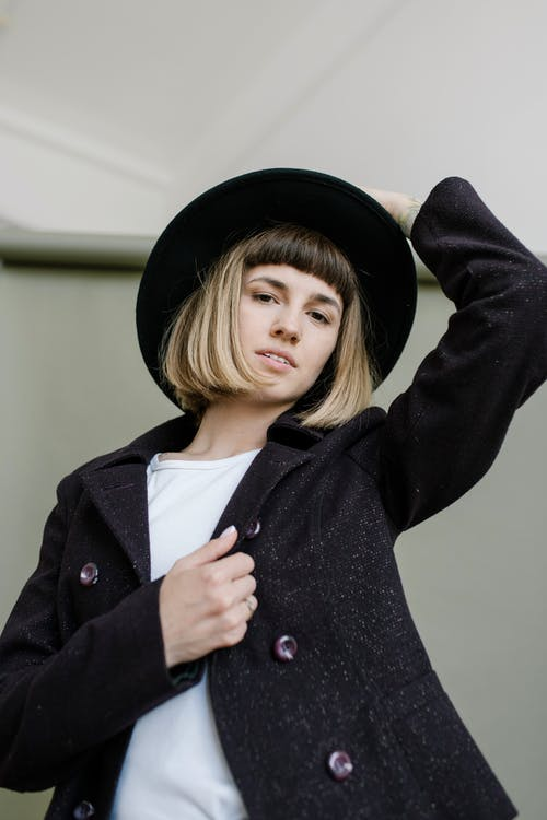 Low angle of young female with modern hairstyle in trendy outfit looking at camera