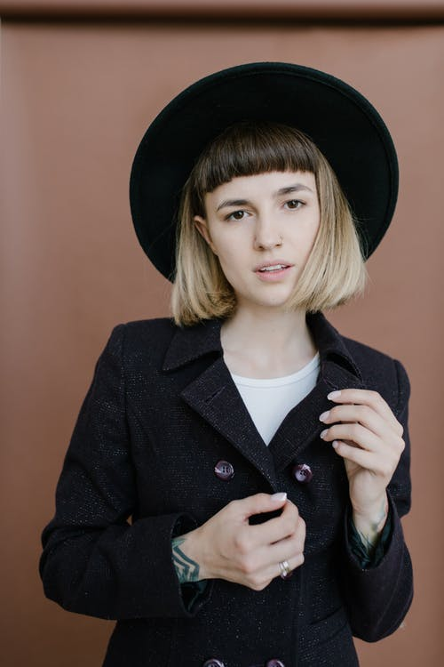 Young attractive female with stylish haircut standing near wall and looking at camera