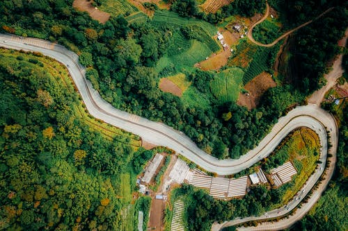 Drone view of curvy roadway near green lush forest and green grassy terrain in countryside