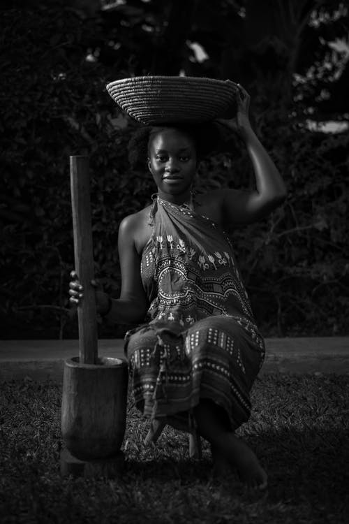 Black and white full body of African barefoot female in traditional clothes sitting with old utensil