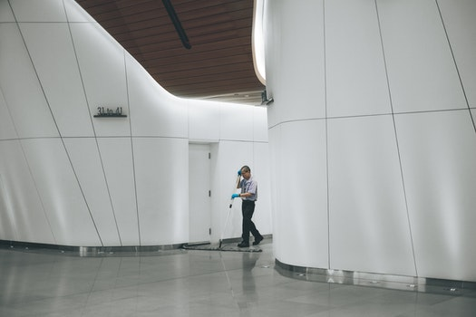 Man in Teal Gloves Walking on Empty Hallway Inside Building