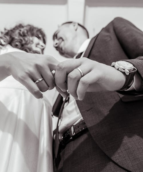 Cheerful newlywed couple with rings on fingers