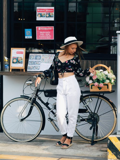 Woman in Black and White Floral Long Sleeve Shirt and White Pants Standing Beside Black Bicycle