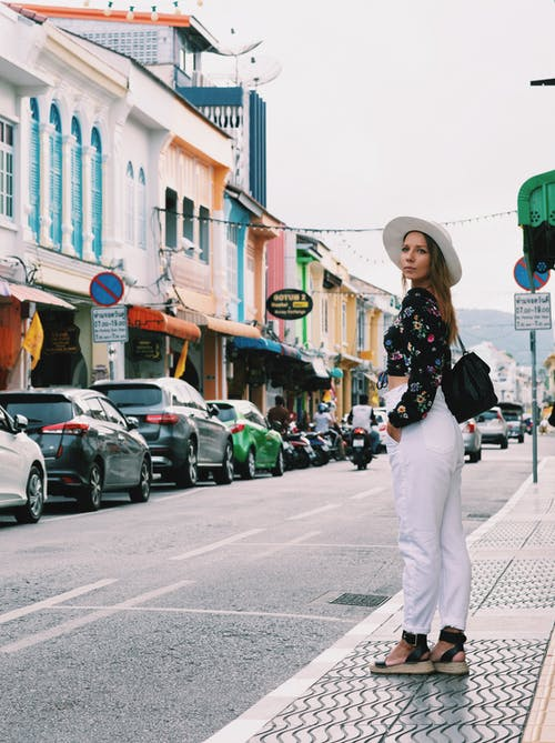 Woman in Black and White Floral Shirt and White Pants Walking on Street