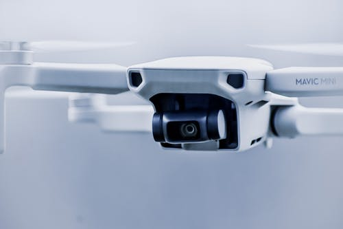 Small contemporary white drone with digital camera flying in light studio against blurred background